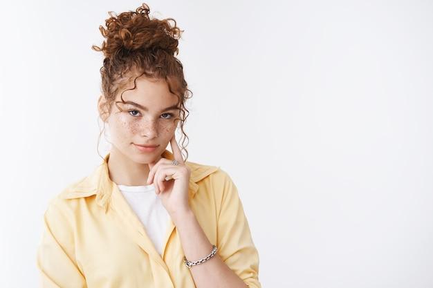 生意気で自信に満ちた見栄えの良い赤毛の生姜の女の子のそばかすを引き付け、額の下で頬を右に触るように説得する、しっかりとした自信のある視線を与えます、思慮深いプロの態度