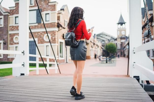 Привлекательная темноволосая туристическая девушка гуляет по улице старого города с мобильным телефоном в руках, просматривая приложение с картами