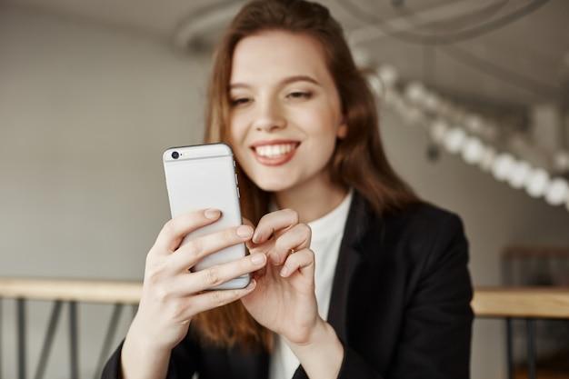 Привлекательная офисная дама сидит в кафе со смартфоном