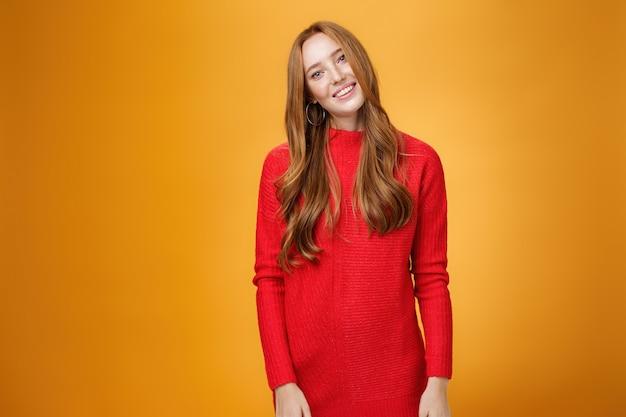 Attraente ed elegante donna d'affari elegante con i capelli rossi in abito lavorato a maglia rosso inclinando la testa e sorridendo civettuola e felicemente in posa su sfondo arancione mentre ascolta con interesse la conversazione