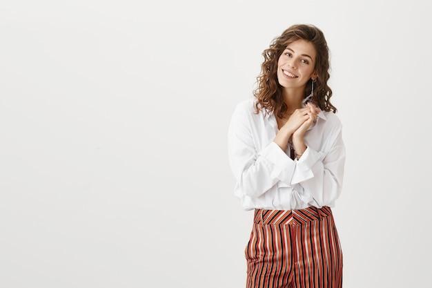 Donna attraente che sembra toccata, lieta di ricevere complimenti