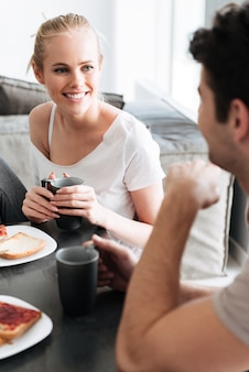 Attrcative cheerful lady looking at her man while they have breakfast