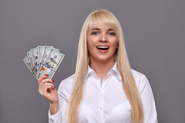 Attreactive emotionally female showing dollars banknotes at came