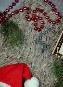 灰色の背景のレイアウトでクリスマス新年の属性。ビーズと鹿の横にあるトウヒの枝。