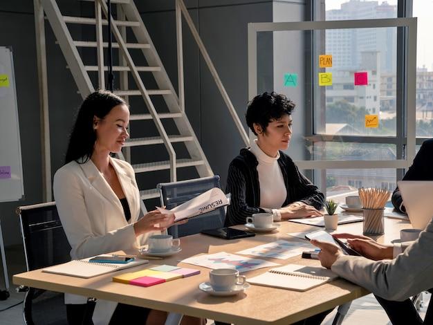 Привлекательные деловые женщины слушают презентацию с командой, работающей в конференц-зале в офисе, бизнес-анализ и концепция стратегии, женщина-лидер