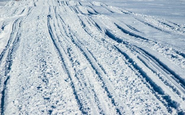 서리가 내린 겨울 날 눈 속에서 atv와 스키 트랙