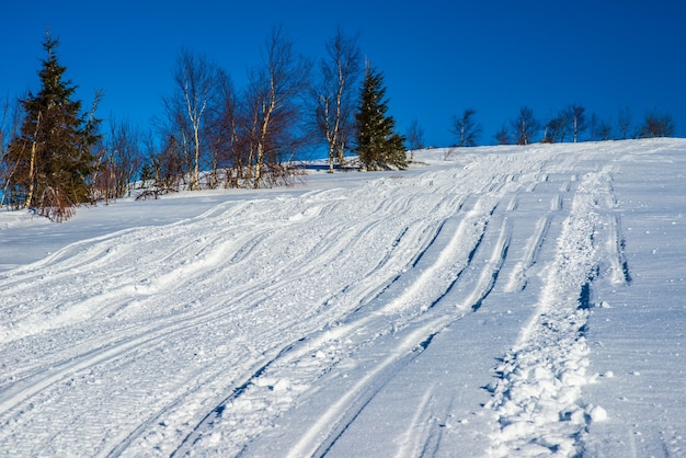 맑은 서리가 내린 겨울 날 눈 속에서 atv 및 스키 트랙. 유럽의 겨울 산에서 휴식의 개념.