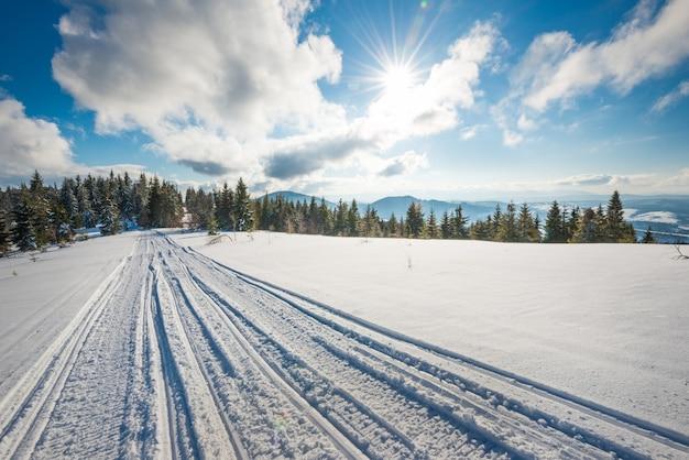 Вездеход и лыжные трассы на снегу в солнечный морозный зимний день