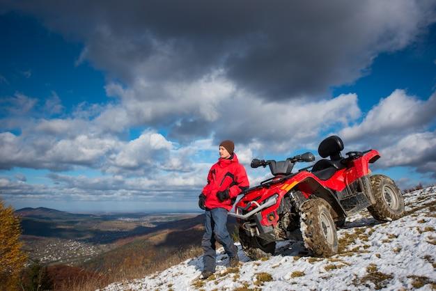 Atv quad bike near guy on snowy mountain slope