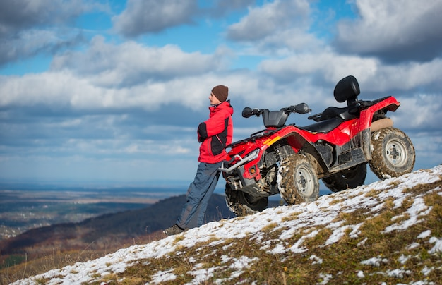 Atv quad bike near man looks into the distance on snowy mountain slope in front of blue cloudy sky with copy space
