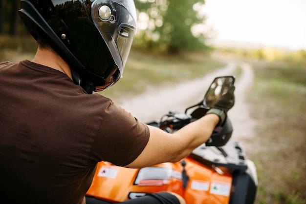 Atvライダーは、旅行前にバックミラーを調整します。クワッドバイクでのオフロード走行、アクティブなエクストリームモータースポーツ