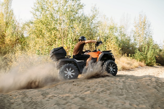 Atv rider in helmet rides on sandy road in forest. riding on quad bike, extreme sport and travelling, quadbike adventure