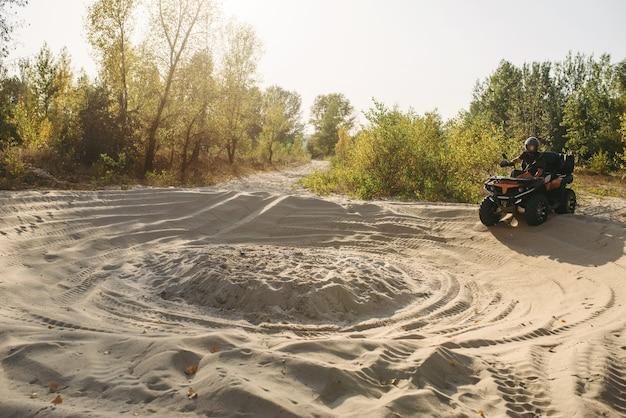 森の砂の道を登るヘルメットのatvライダー