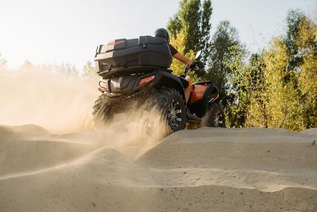 砂の採石場、ほこりの雲、クワッドバイクに乗るatv