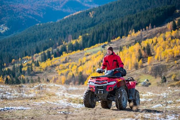 男は山の道でatvに乗っています。