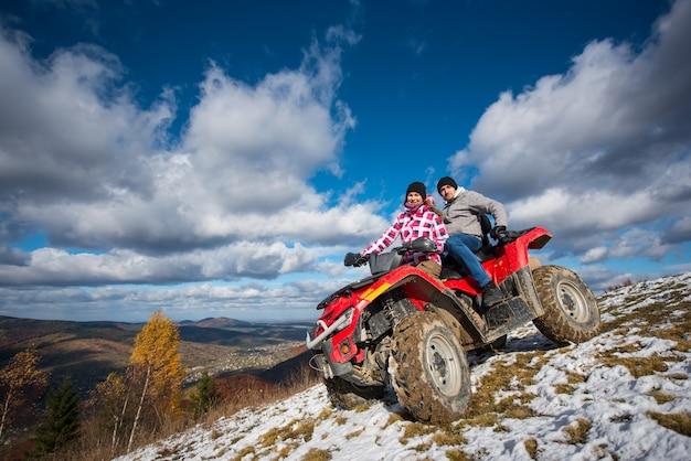 山の斜面に赤いatvに乗って冬服のカップル