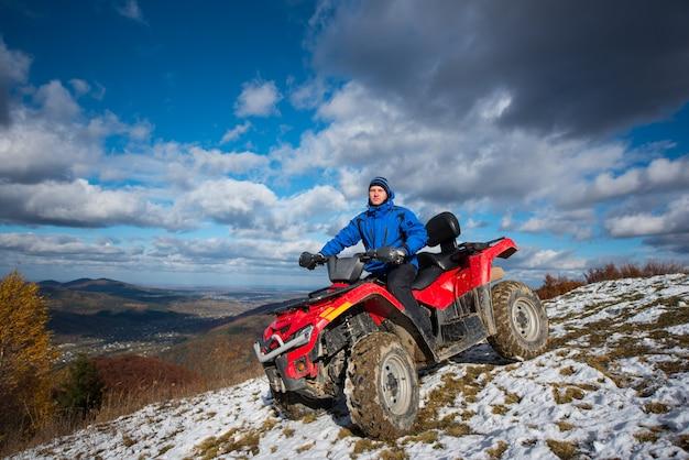 晴れた日に雪をかぶった峰から下りてくるatvの男。