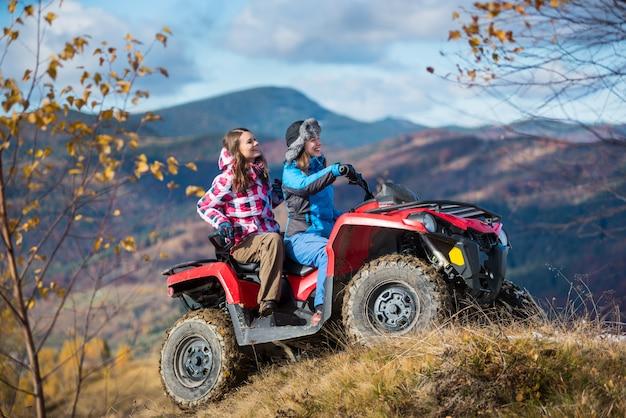 雪の丘でatvを運転する幸せな女性