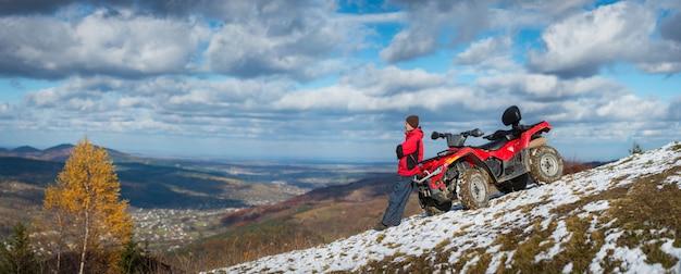 パノラマ。雪に覆われた山の上にatvクワッドバイクの近くに立っている人