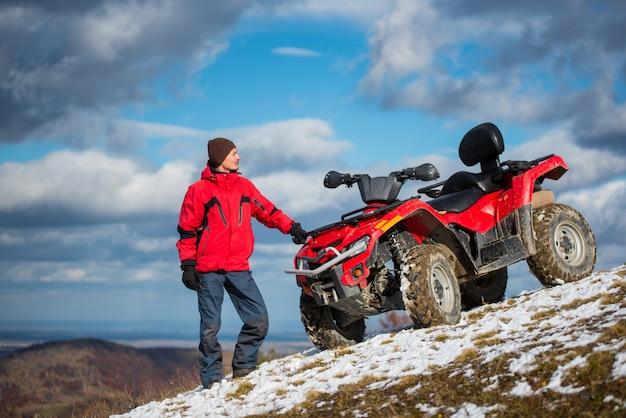 雪に覆われた丘の上のatvの近くの冬服で立っている人