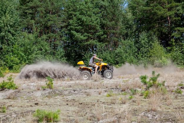 砂浜の森で黄色の四輪バギーatv全地形車両に乗る男。エクストリームスポーツモーション、アドベンチャー、観光名所。