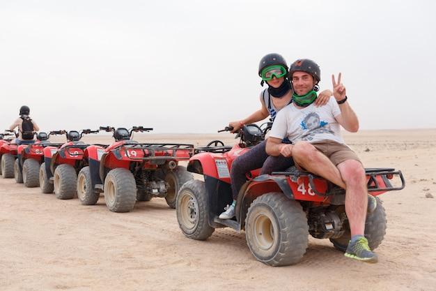 砂のatvに乗って若いカップル