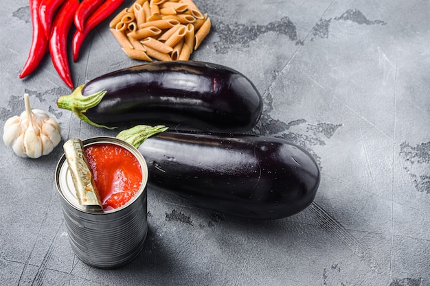 Aubergine penne ingredients eggplant pasta, pepper tomatoe sauce, on grey background side view space for text.