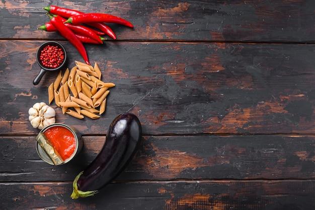 茄子ペンネ成分ナスパスタ、コショウトマトソース、古い木製のテーブルトップビューのテキストのためのスペース。