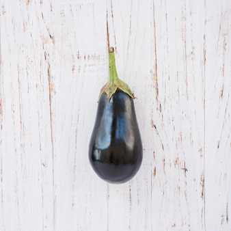 Aubergines on white wooden textured backdrop