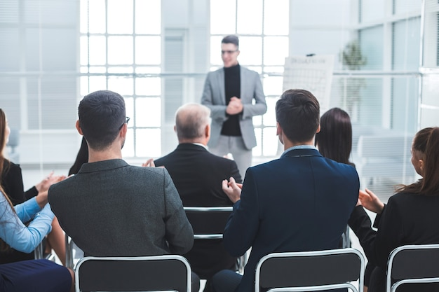 청중은 비즈니스 프레젠테이션 중에 발표자에게 박수를 보냅니다. 비즈니스 및 교육