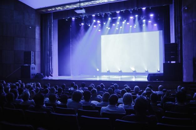 Зрители в конференц-зале ждут выступления спикера и смотрят на пустую сцену.