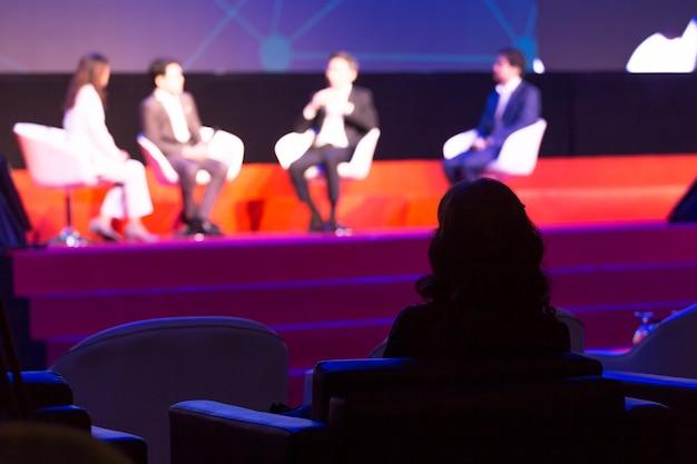 観客は、会議室やセミナーの会議、ビジネスや教育の概念でステージ上のスピーカーを聞いています