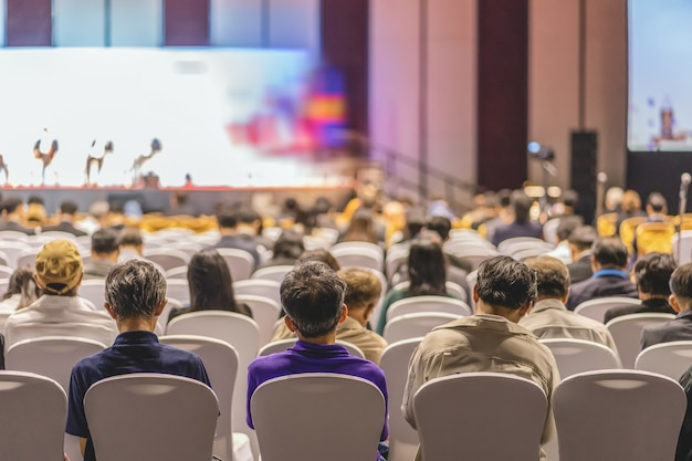 Audience listening speakers on the stage in the conference hall