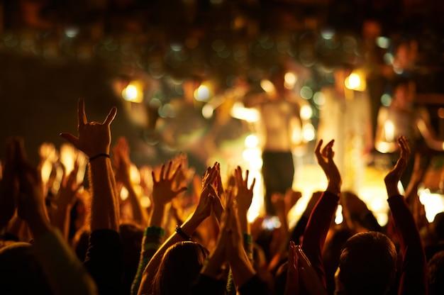 Аудитория с поднятыми руками на музыкальном фестивале и огнями, стекающими сверху над сценой.