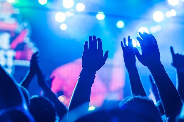 音楽祭で挙手し、ステージの上からライトが降り注ぐ観客。