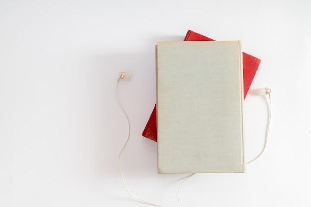 オーディオブックのコンセプト。ヘッドフォンと白いテーブルの背景の上の本。