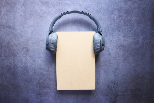 Концепция аудио книги. наушники и книга над деревянным столом.