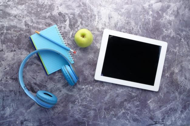 オーディオブックのコンセプト。テーブルの上のヘッドフォンとデジタルタブレット。