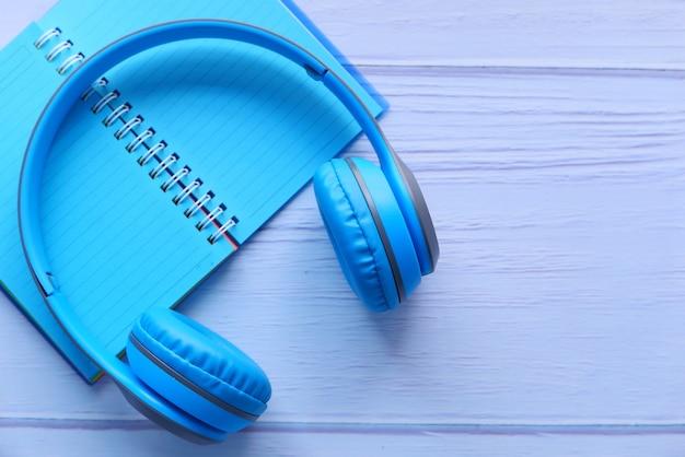 Концепция аудиокниги. наушники и блокнот на белом фоне