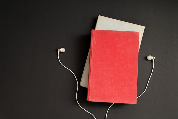 Audio book concept. headphones and book over black table.