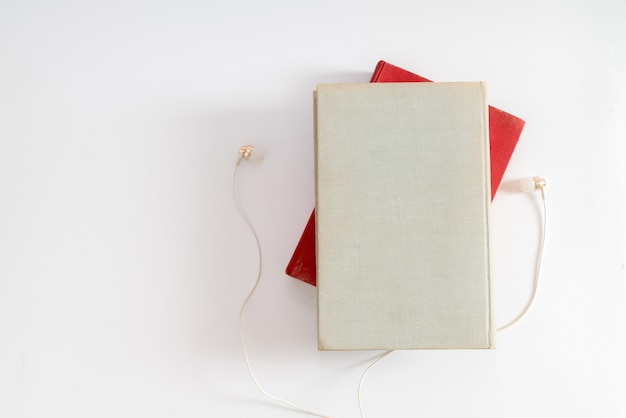 Audio book concept. headphones and book over white table background.