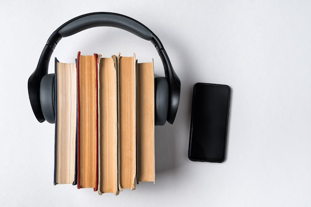 Audio book concept. headphones worn on a stack of old books and mobile phone. white background, copy space top view