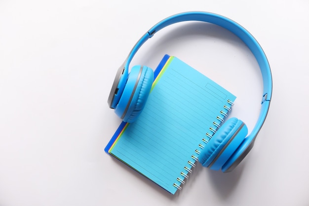 Audio book concept with headphones and notepad