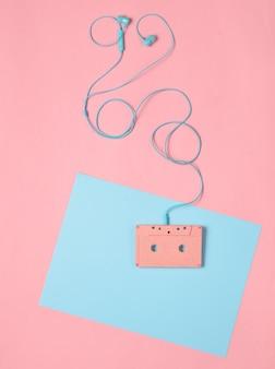 오디오 카세트 및 블루 핑크 파스텔 배경에 이어폰. 뮤지컬 개념입니다. 레트로 스타일. 미니멀리즘. 평면도