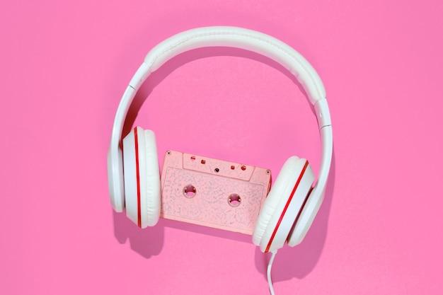 오디오 카세트와 분홍색 배경에 헤드폰입니다. 복고풍 음악 개념입니다. 빈티지 배경입니다. 디스코 파티. 평면도