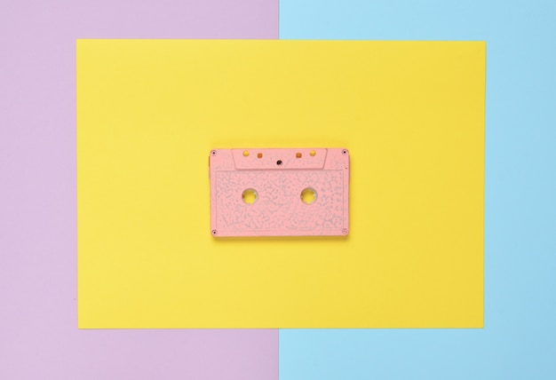 Audio cassette on a colored paper background. retro media technology 80s. music, entertainment. top view. minimalism trend