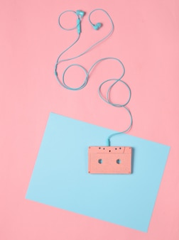 Audio cassette and earphones on a blue pink pastel background. musical concept. retro style. minimalism. top view