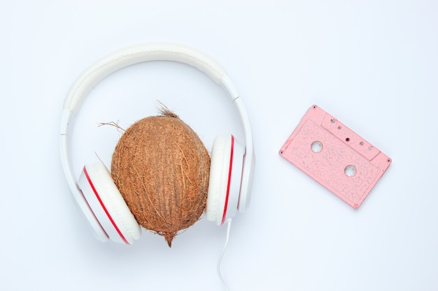 Audio cassette and headphones with coconut on white background. retro music concept. vintage background. disco party.