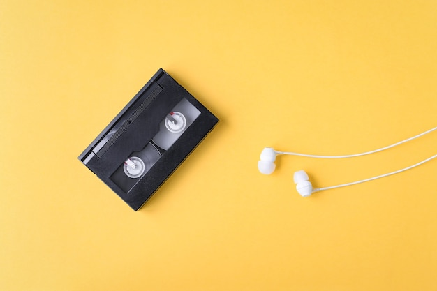 Audio cassette and headphones on a yellow background nostalgic times