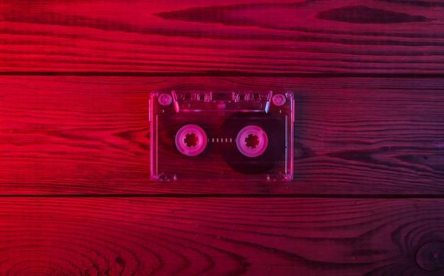 木製の表面にオーディオカセット。ネオンの赤と青の光